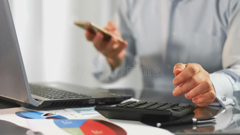 Financial expert calculating taxes holding smartphone in hand, office work. Stock photo royalty free stock image
