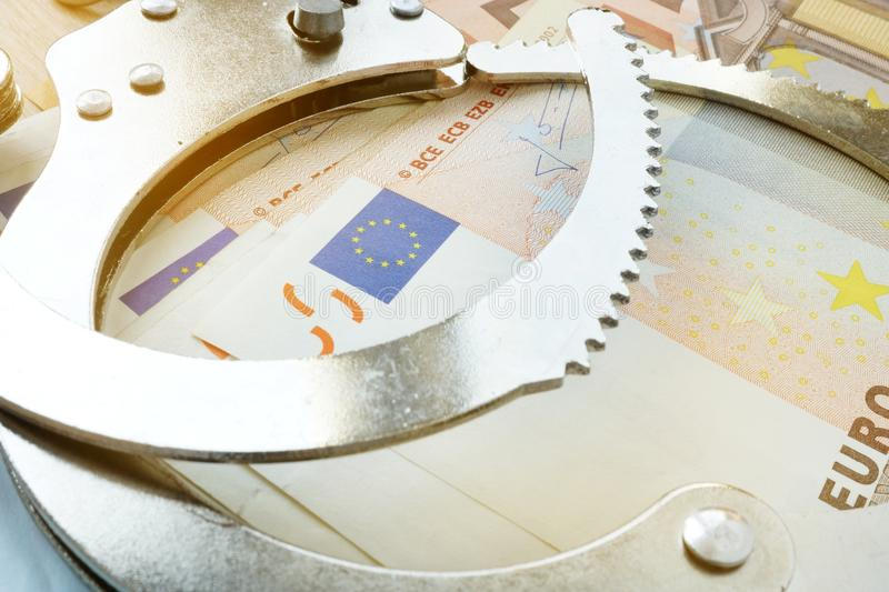 Financial fraud in EU. Handcuffs and euro bills. royalty free stock photography
