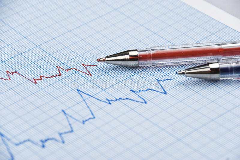 Financial graph. Financial chart shows a graph in two colors red and blue with two pens made on millimeter paper,selective focus stock image