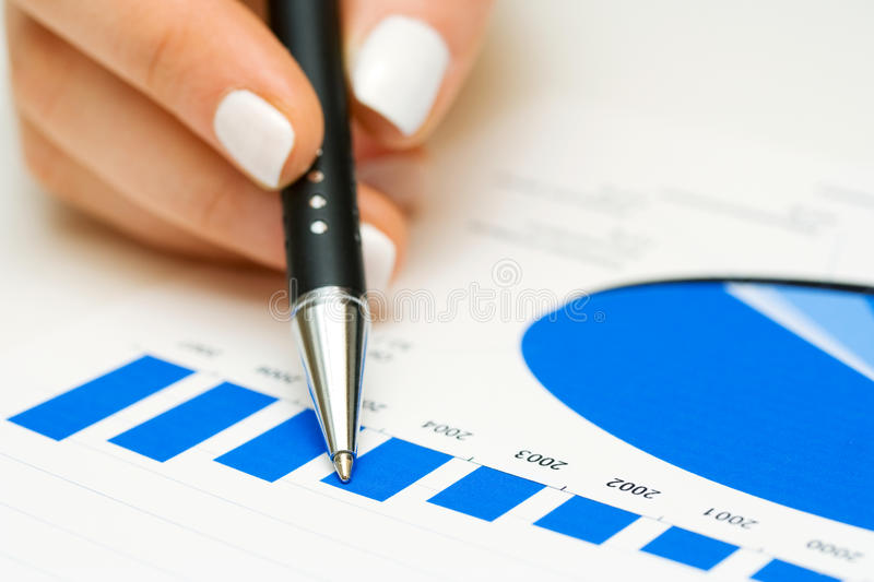 Financial graphs analysis. Female hand analyzing stock market graphs royalty free stock image
