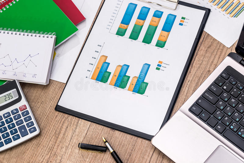 Financial graphs with laptop, calculator, pen stock photography