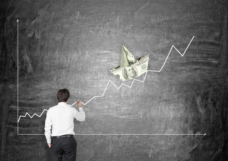 Financial growth. Businessman drawing positive business chart with dollar banknote boat on chalkboard background. Financial growth concept stock image