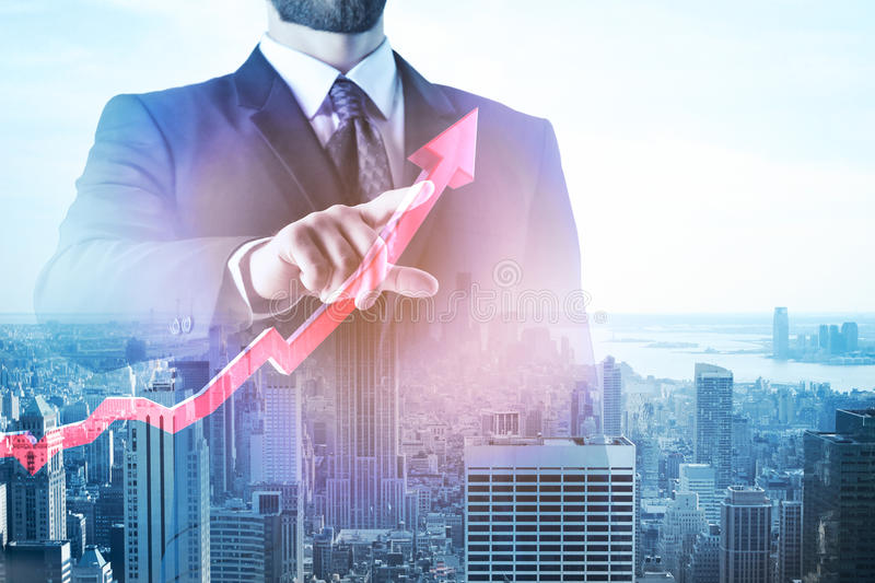 Financial growth concept. Abstract image of businessman pointing at upward red chart arrow on city background. Financial growth concept. Double exposure royalty free stock images