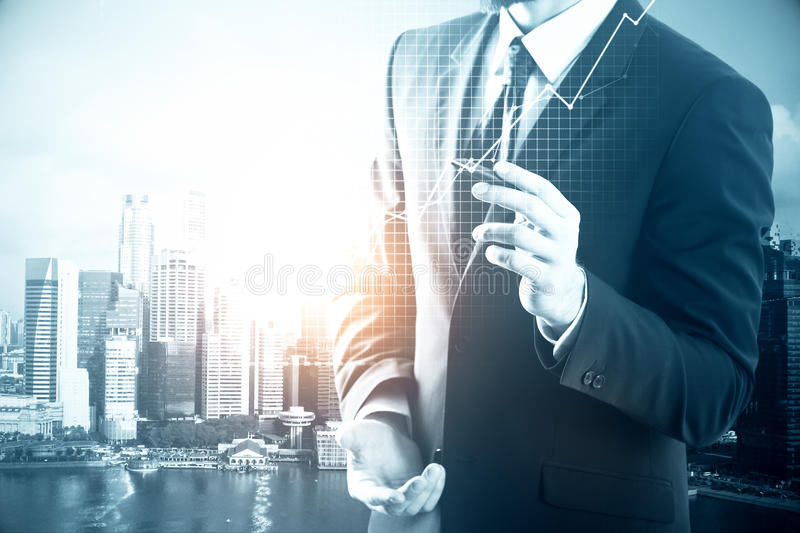 Financial growth concept. Businessman drawing business chart on city background. Financial growth concept royalty free stock images