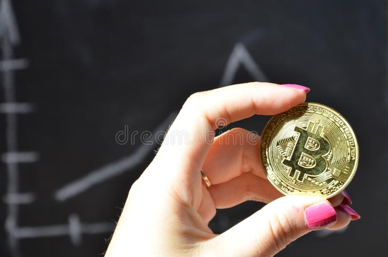 Financial growth concept with golden Bitcoins ladder on forex chart background. new virtual money. coin of crypto currency. electr. Onic money. female hand holds royalty free stock photo