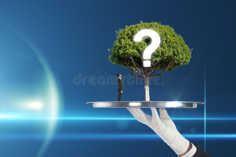 Financial growth concept. Hand holding abstract tray with tree, question mark and thinking businessman on blue background. Financial growth concept royalty free stock image