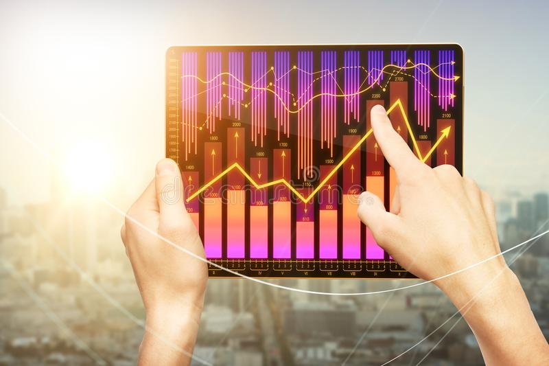 Financial growth concept. Male hands pointing at tablet with forex chart on abstract blurry city background with sunlight. Financial growth concept royalty free stock photo