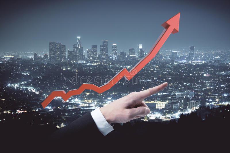 Financial growth concept. Red chart arrow and businessman finger pointed up on illuminated night city background. Financial growth concept stock photo