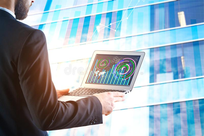 Financial growth concept. Side view of businessman using laptop with business chart. City building background. Financial growth concept. Double exposure stock photos