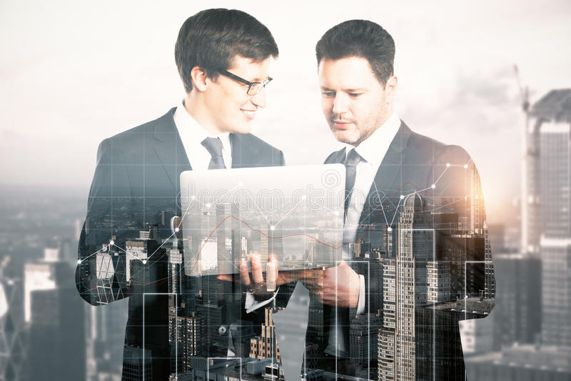 Financial growth concept. Two handsome cheerful businessmen using laptop on abstract city background with business chart. Financial growth concept. Double stock image