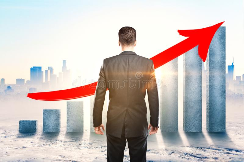 Financial growth and development concept. Back view of businessman looking at concrete chart bars with upward red arrow on city background with sunlight royalty free stock images