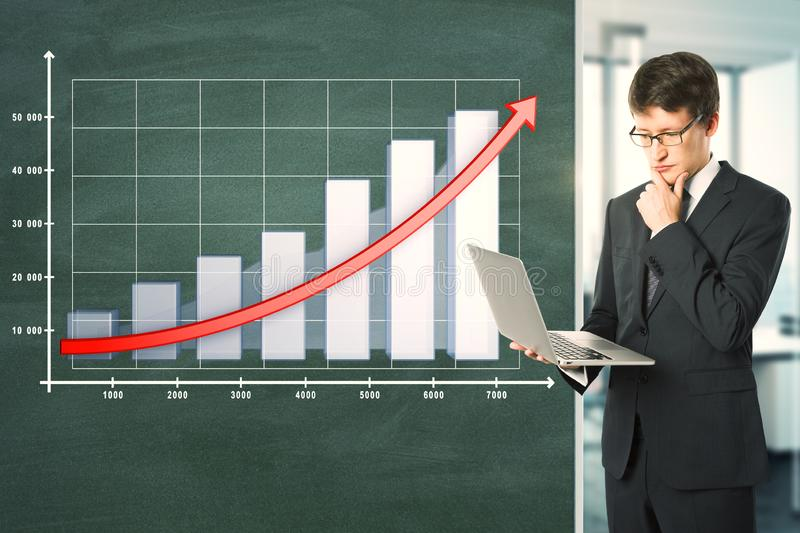 Financial growth and presentation concept. Attractive young businessman with laptop standing next to blackboard with business chart and arrow. Financial growth stock photos