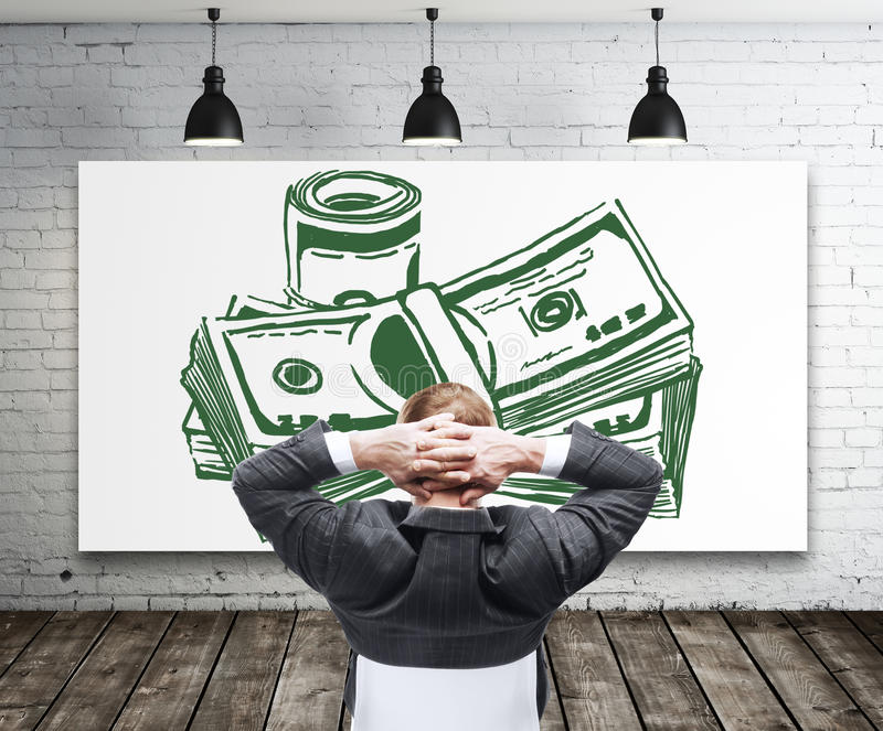 Financial growth and success concept. Relaxing young businessman looking at creative dollar bill sketch in modern interior with white brick walls, wooden floor royalty free stock image