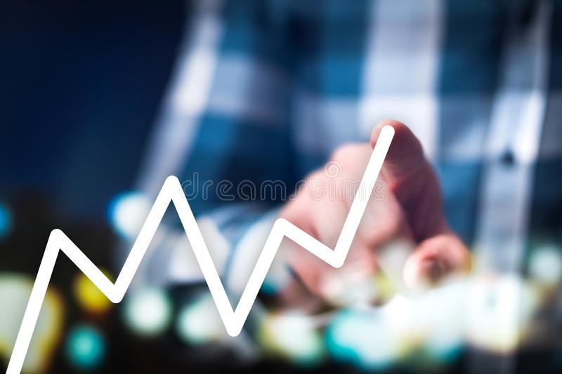 Financial growth, success and progress concept. Business man drawing growing and increasing graph with finger in futuristic, modern and abstract space. Digital stock photography