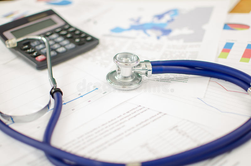 Financial health. Stethoscope and calculator placed on financial charts stock images