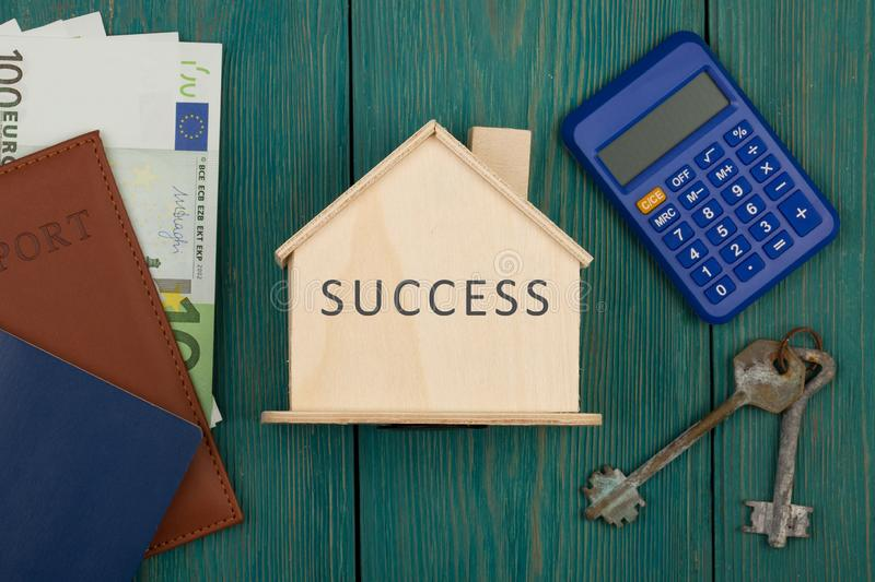 Financial independence - little house with word Success, keys, calculator, passport, money. On blue wooden desk, euro, currency, marketing, finance, privacy royalty free stock photography