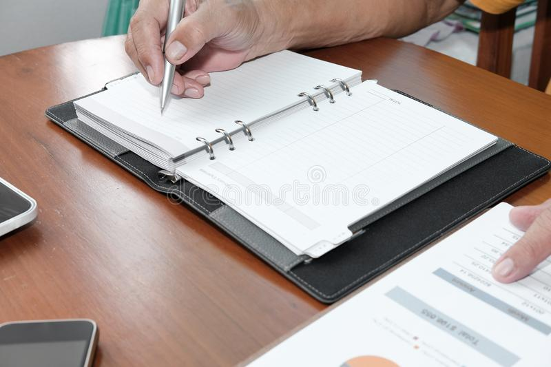 Financial inspector analyze sales document at office. man writing note on notebook. At workplace stock image