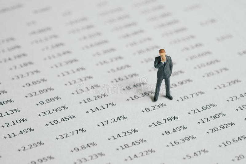Financial and investment career, miniature businessman standing and thinking on printed numbers percentage of profit report.  royalty free stock image