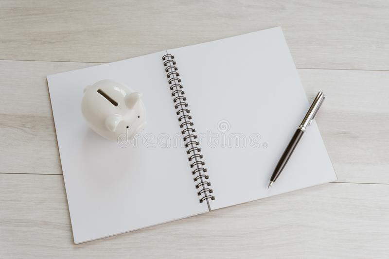 Financial, investment plan, budget or saving target list, pening white blank paper note book with pen on the right and piggy bank. On the left on light grey stock photos