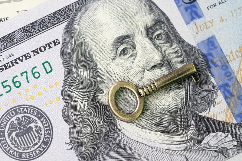 Financial key value, world economics growth or stock market investment ideas concept, bronze vintage key on Benjamin Franklin. Face in USA 100 dollar banknote royalty free stock photography