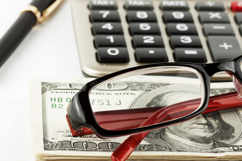 Financial Literacy. Closeup Pen, calculator, cash and glasses stock photography