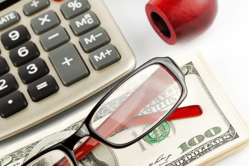 Financial Literacy. Closeup Pen, calculator, cash and glasses stock photo