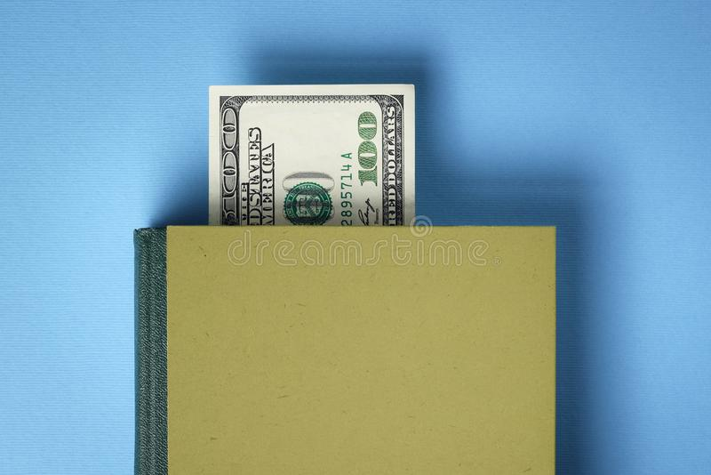 Financial Literacy Concept. Business book on financial literacy and success. Bookmark from the dollar bill. Concept with blank book cover stock image