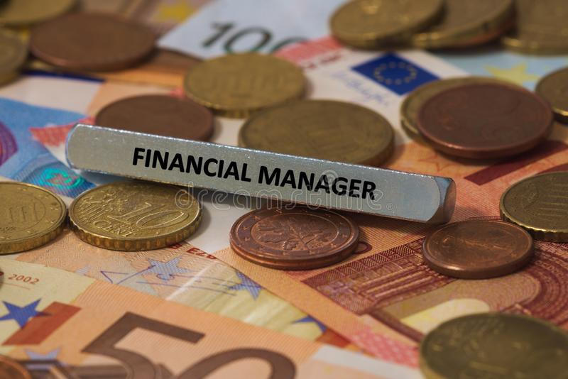 Financial manager - the word was printed on a metal bar. the metal bar was placed on several banknotes. Series of words printed on a metal bar. the metal bar was royalty free stock image