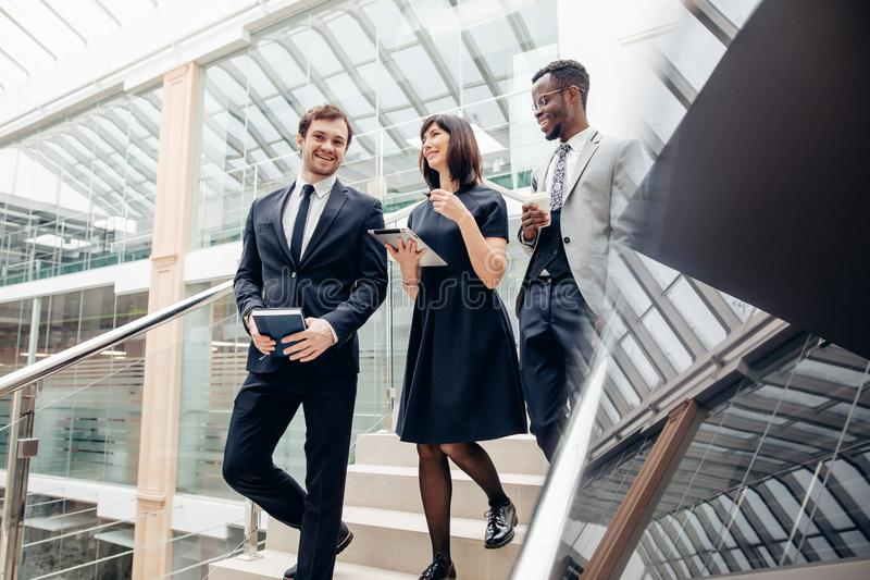 Three multiracial business people walking down on stairs with digital tablet. Financial multiethnic team members going down stairs with tablet and smartphone stock image