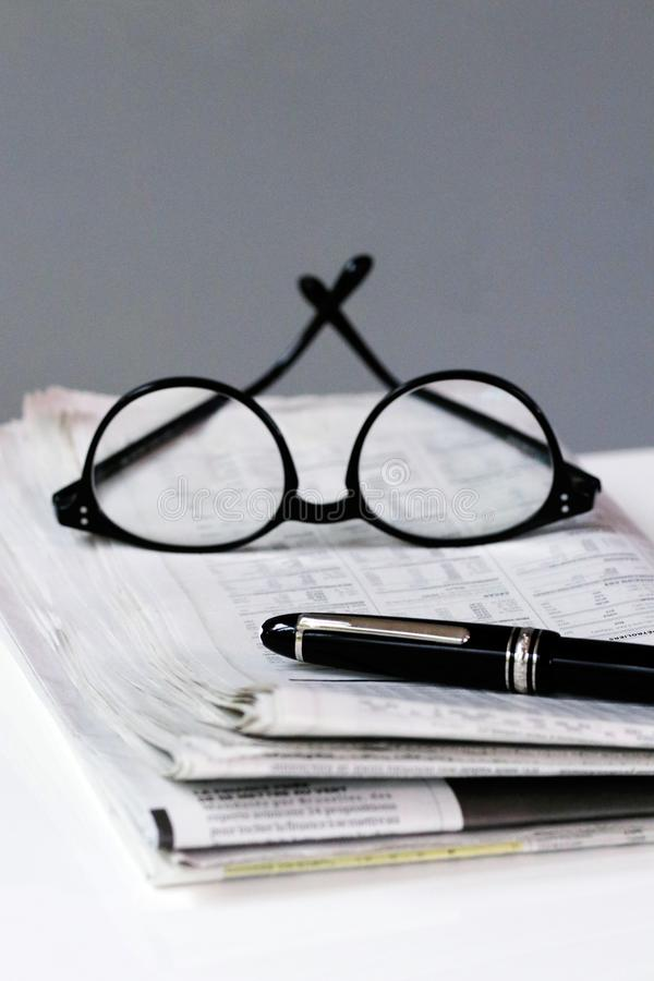 Financial newspaper break background with pen and glasses business man royalty free stock photo
