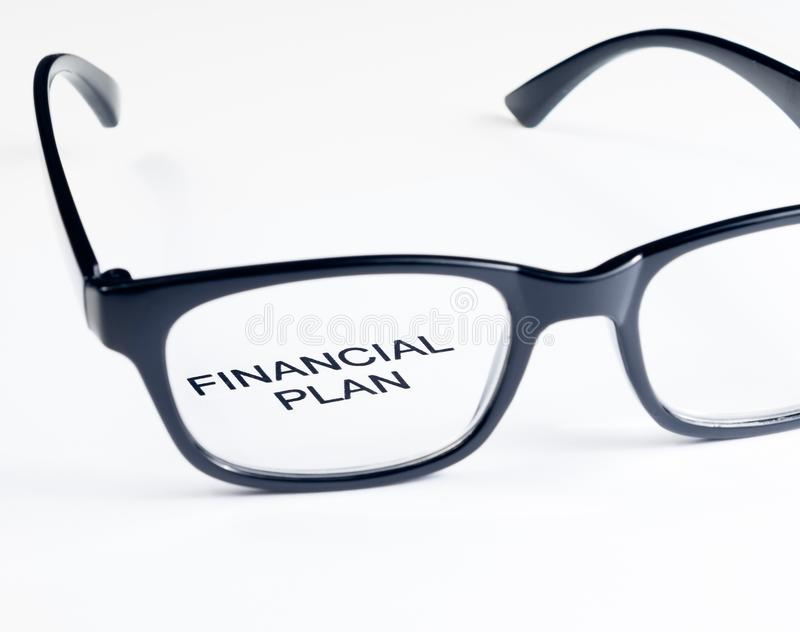 Financial plan words see through glasses lens, business concept. Financial plan words see through glasses lens on white background, business concept royalty free stock photo
