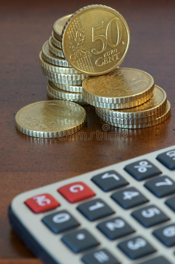 Financial Planning. A stack of 50 cents euro coins and a calculator. Focus on currencies royalty free stock photography