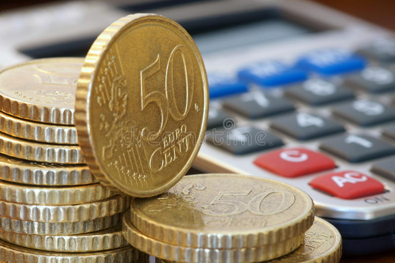 Financial Planning. A stack of 50 cents euro coins and a calculator royalty free stock images
