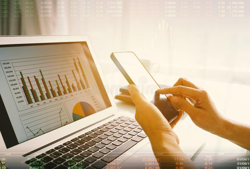 Financial planning concept. Double exposure analysts use mobile smartphones and business graphs to display successful financial planning stock photography