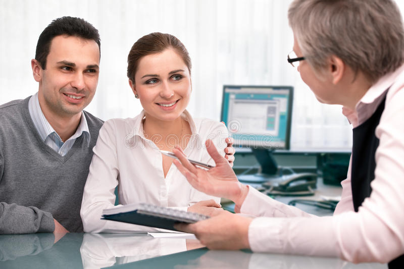 Financial planning consultation. Cheerful young couple at financial planning consultation stock photography
