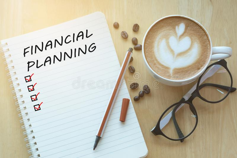 Financial Planning message and check list marks on notebook, glasses, pencil and coffee cup on wooden table with sunlight in. The morning. Business concept. and royalty free stock image