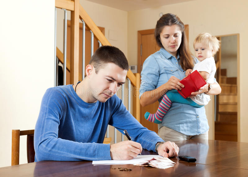 Financial problems in family. Sad women wit baby against husband at table with money stock image