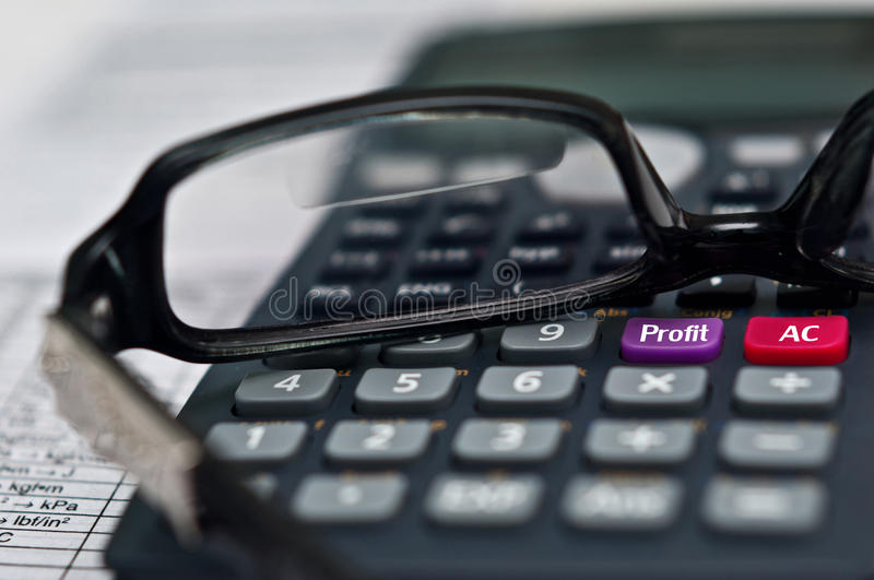Financial report 2. A calculator with a profit button with reading glasses on financial report royalty free stock image
