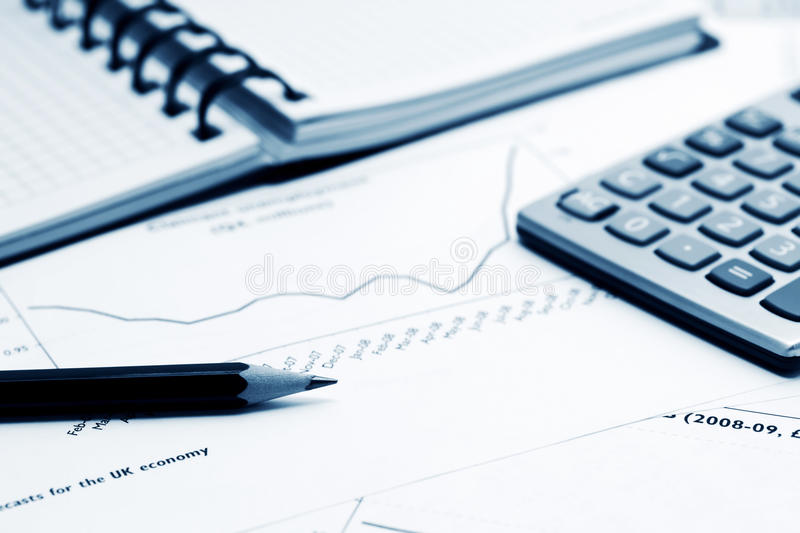 Financial reports and accounting. Calculator, pencil and stock market graphs and charts analysis stock photography