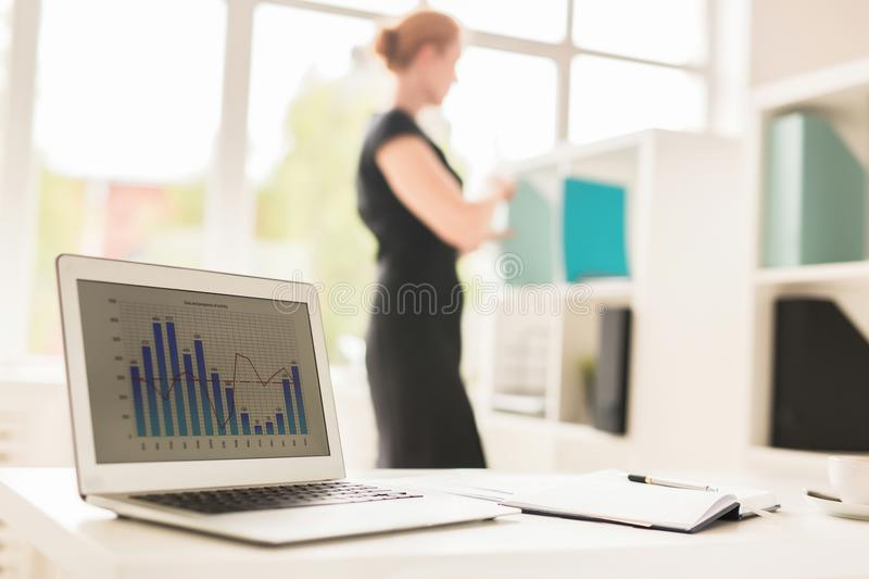 Financial research. Laptop at workplace of analyst with graph and charts on display stock photo