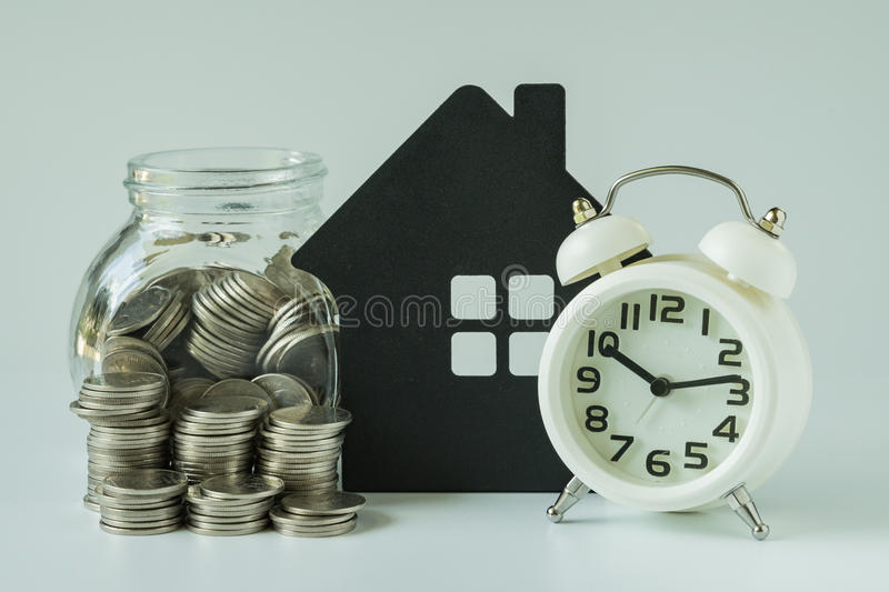 Financial saving or mortgage concept with stack of coins and coins in glass pot with paper house on white background.  stock image