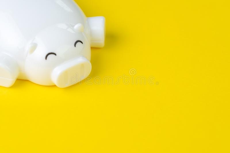 Financial, savings, budget, cost or investment background concept with copy space, white happy smiling piggy bank on vivid yellow. Background, use as easy royalty free stock image