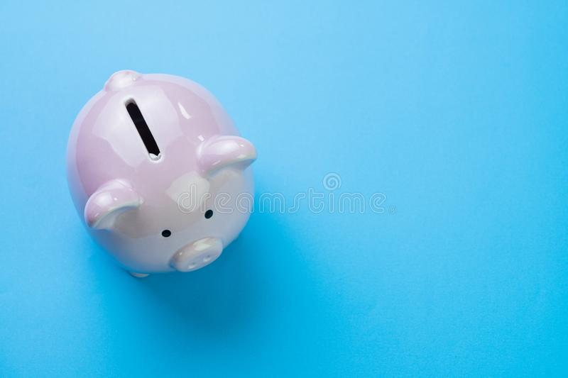 Financial, savings, budget, cost or investment concept, white happy piggy bank on clean blue background with copy space.  stock image