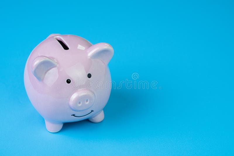 Financial, savings, budget, cost or investment concept, white happy piggy bank on clean blue background with copy space.  stock photography