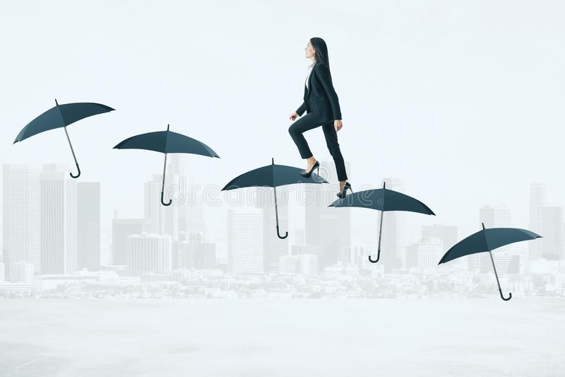Financial security and growth concept. Side view of young businesswoman walking on umbrella ladder on city background. Financial security and growth concept stock photos