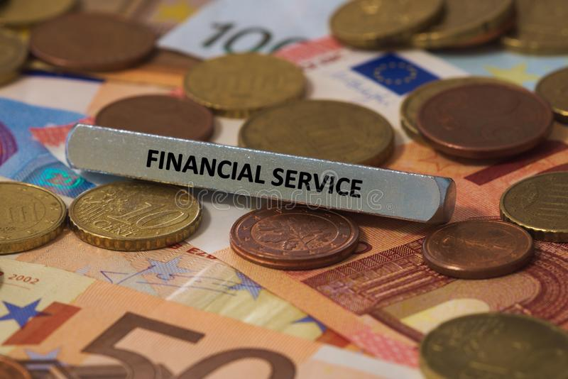 Financial service - the word was printed on a metal bar. the metal bar was placed on several banknotes. Series of words printed on a metal bar. the metal bar was royalty free stock photography