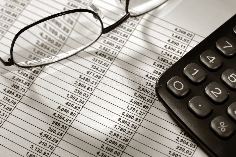 Financial Spreadsheet with Calculator and Glasses. Financial spreadsheet with Dollar number figures in boxed rows and columns with calculator and glasses royalty free stock photo
