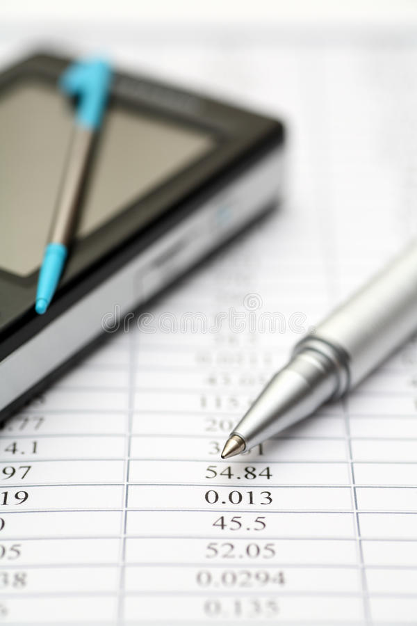 Financial statements. Ballpoint pen and PDA with digitized pen on . Shallow depth of feild. Close-up royalty free stock images