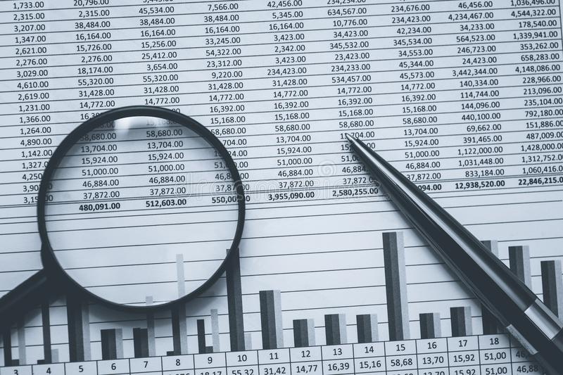 Financial stock banking accountant spreadsheet data in black and white. Conceptual monochrome photo with magnifying glass and bla royalty free stock images