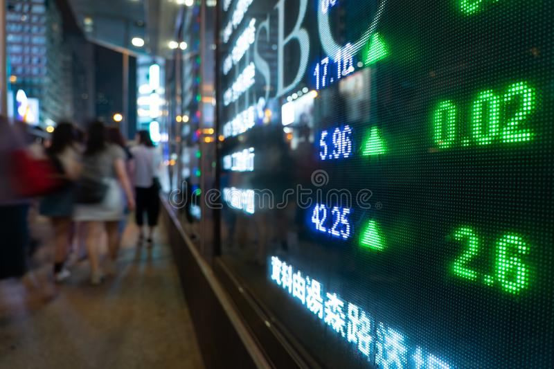 Financial stock exchange market display screen board on the street and city light reflection in Hong Kong stock photo